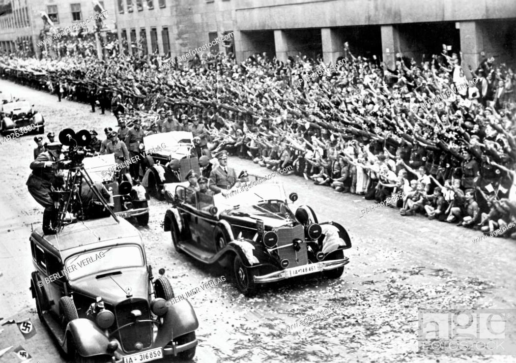 Stock Photo: People cheer at Hitler's victory procession outside of the new Reichs Ministry of Aviation on Wilhelmplatz in front of a crowd of cheering people as Hitler.