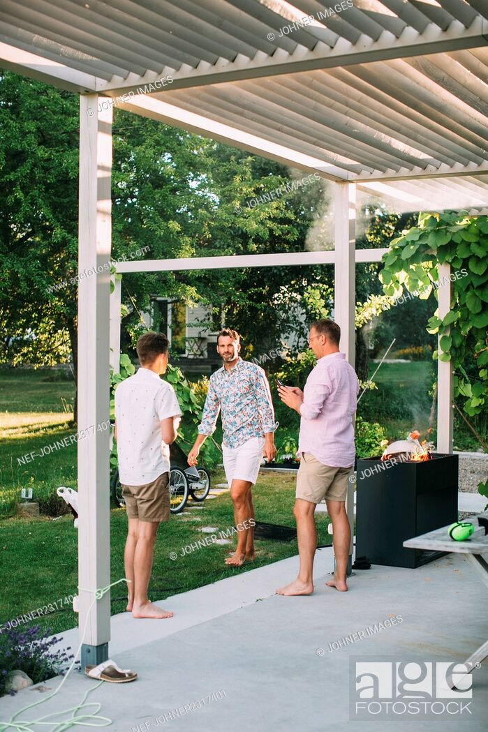 Stock Photo: Men barbecuing in garden.