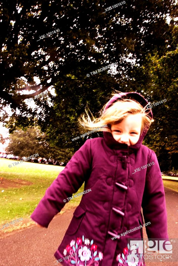 Stock Photo: 5 year girl in park wearing magenta coat in cold windy weather.