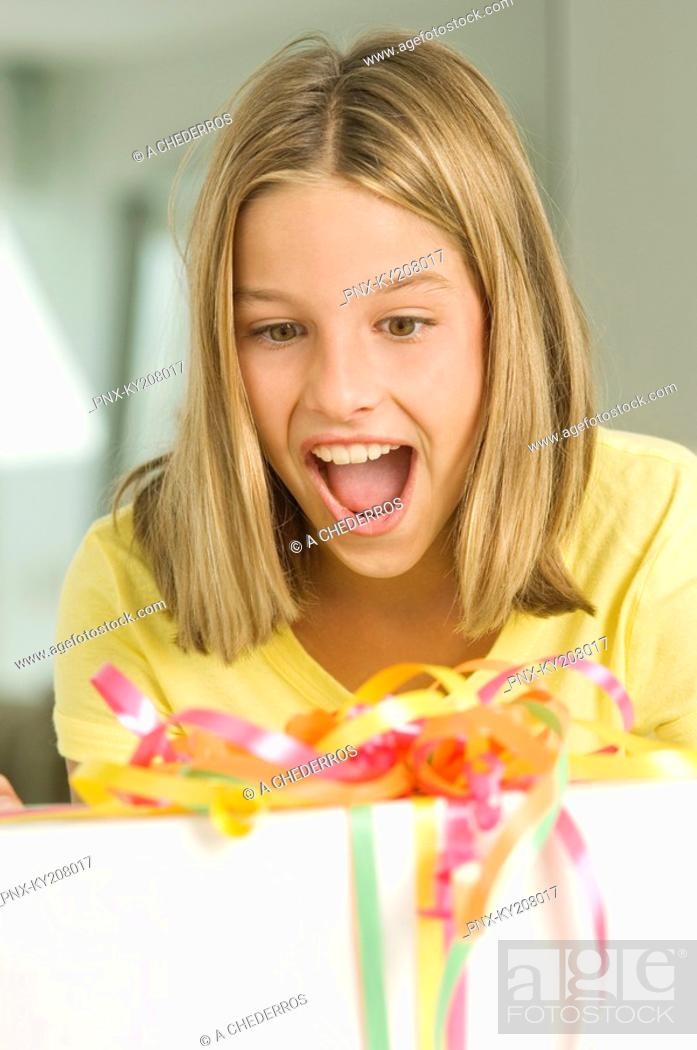 Stock Photo: Girl looking at a birthday present with a surprise.
