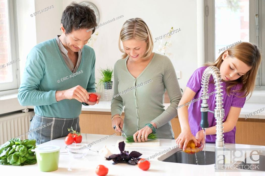 Stock Photo: Family preparing food in the kitchen.