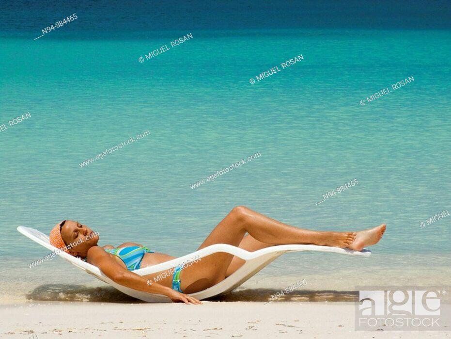 Stock Photo: Girl in hammock taking sun bath on a Caribbean beach.