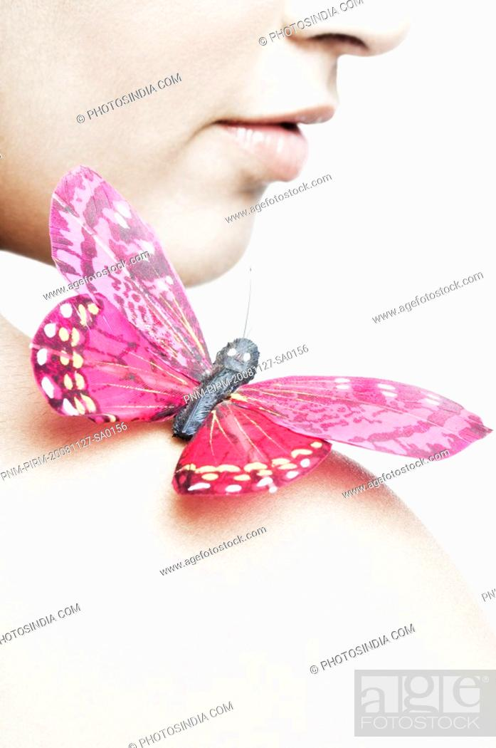 Stock Photo: Close-up of a butterfly perching on a young woman's shoulder.