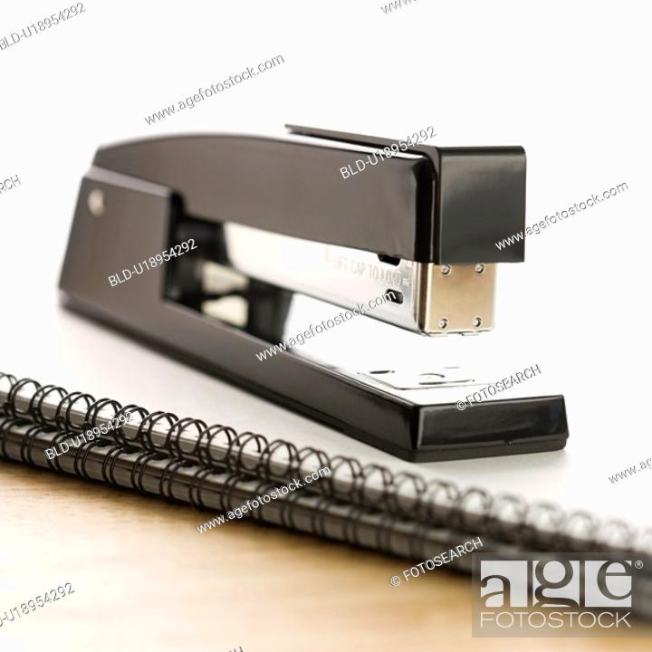 Stock Photo: Black stapler on top of a spiral bound notebook.