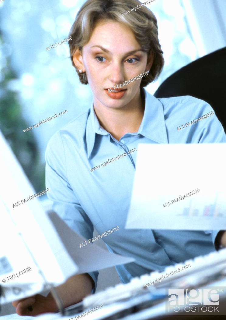 Stock Photo: Businesswoman holding documents, looking at computer.
