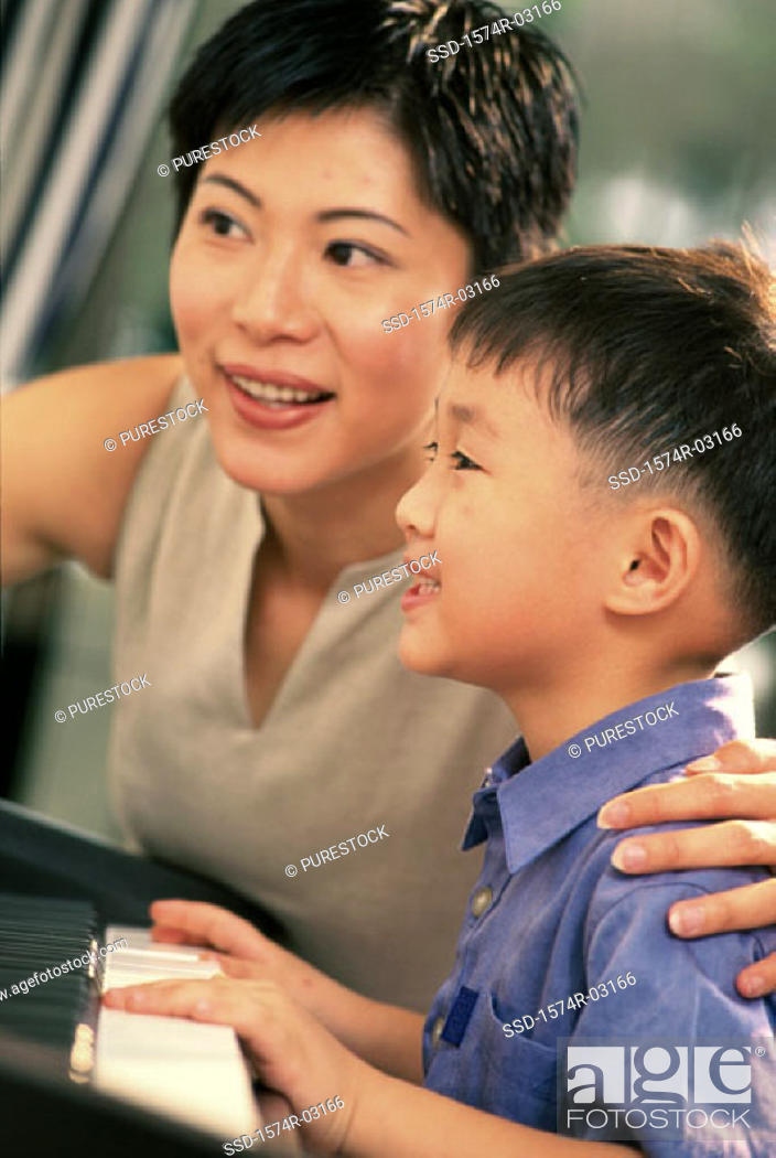 Stock Photo: Mother teaching her son how to play the piano.