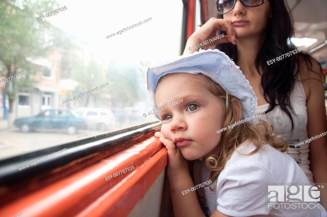 Stock Photo: Little girl and mom goes to tram. Girl tired, thoughtfully, looking out the window.