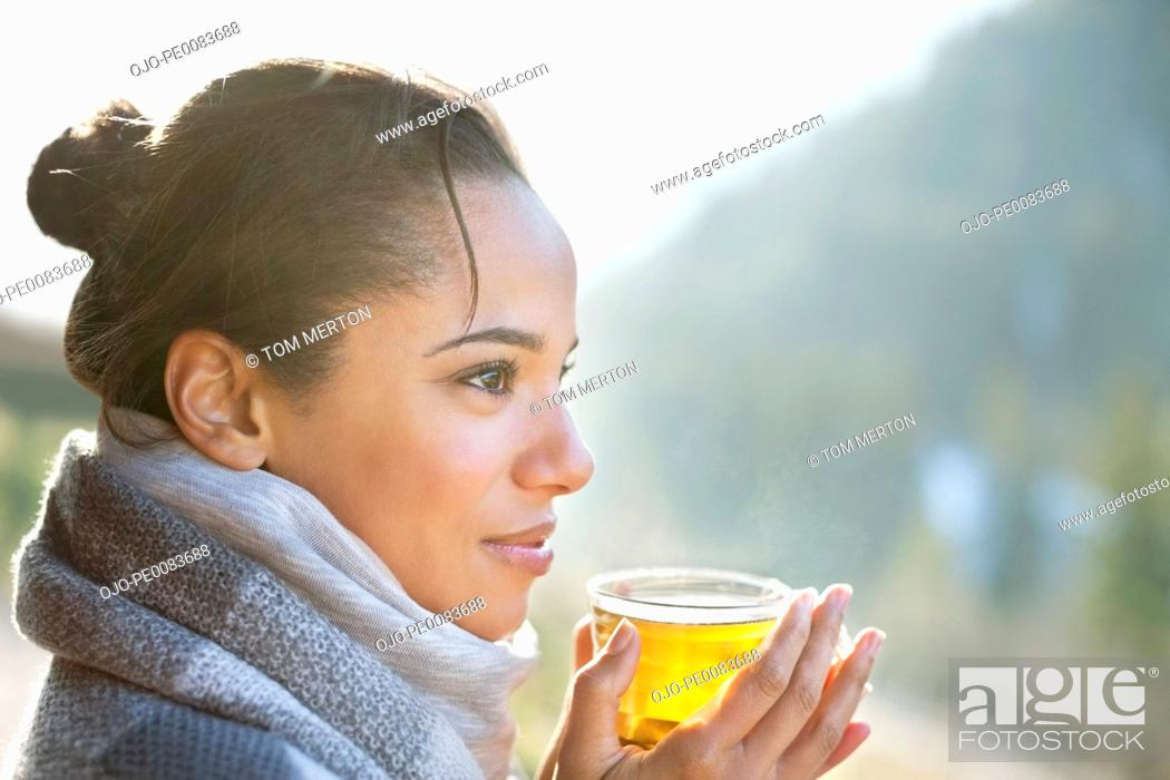 Stock Photo: Close up of smiling woman drinking tea outdoors.