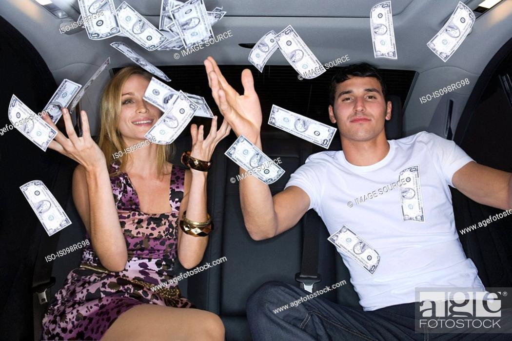 Stock Photo: Wealthy couple celebrating in a car.