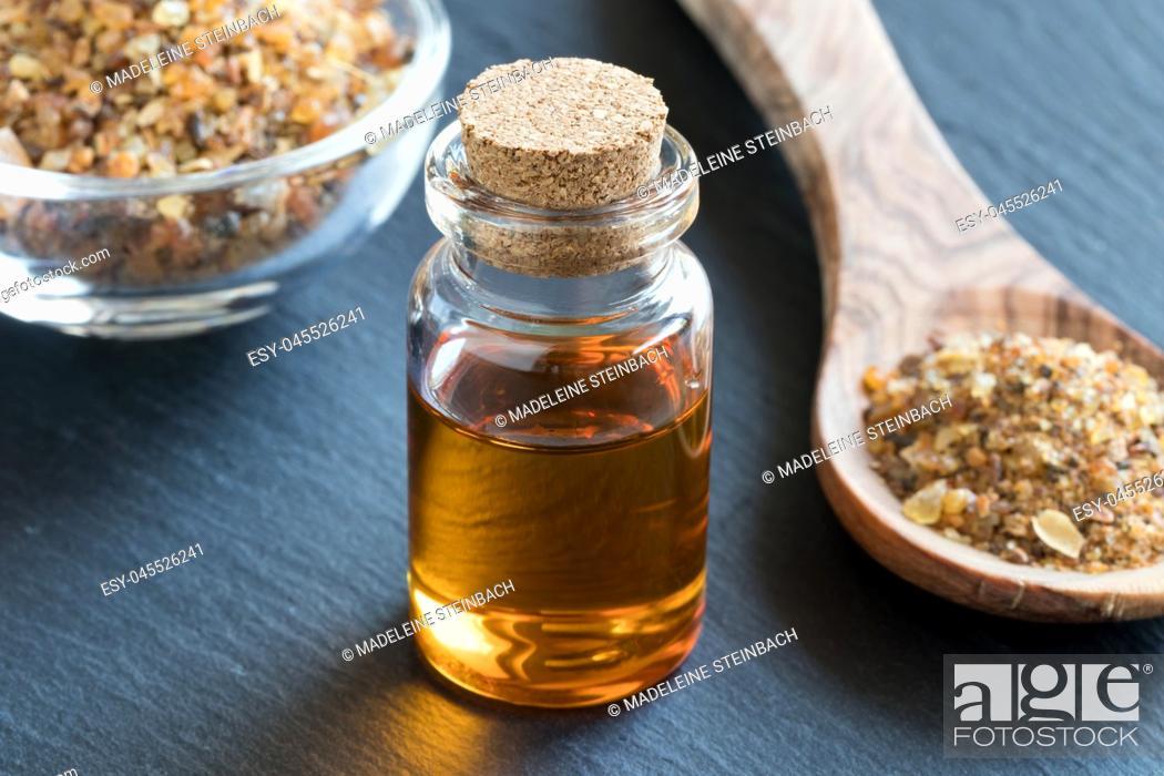 Stock Photo: A bottle of myrrh essential oil with myrrh resin on a dark background.