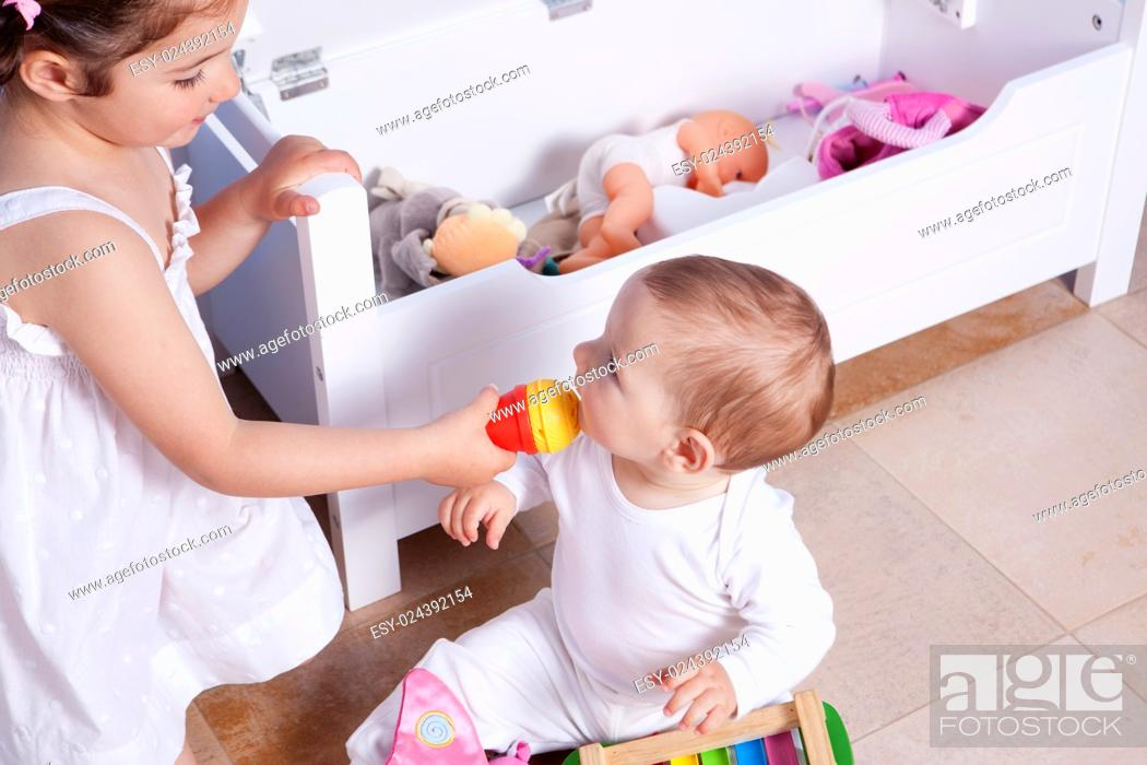 Stock Photo: Baby boy playing with his sister at toys room. They are singing with a toy microphone.