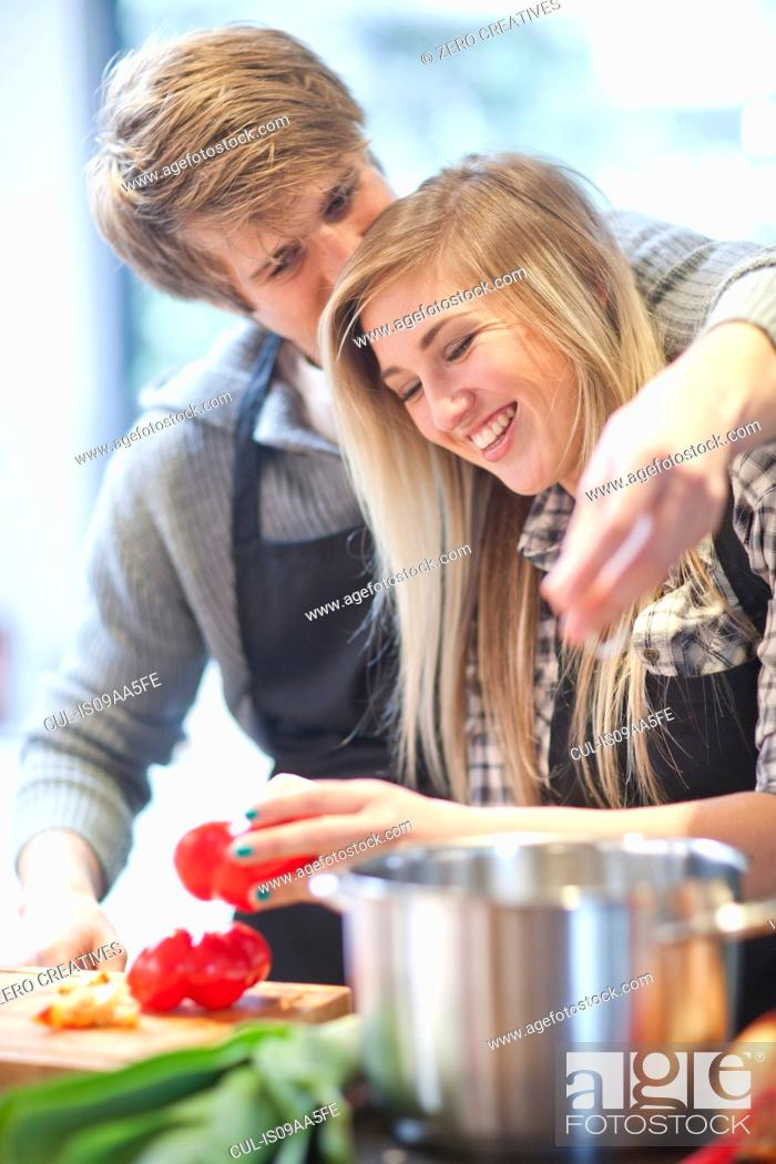 Stock Photo: Affectionate young couple preparing meal.