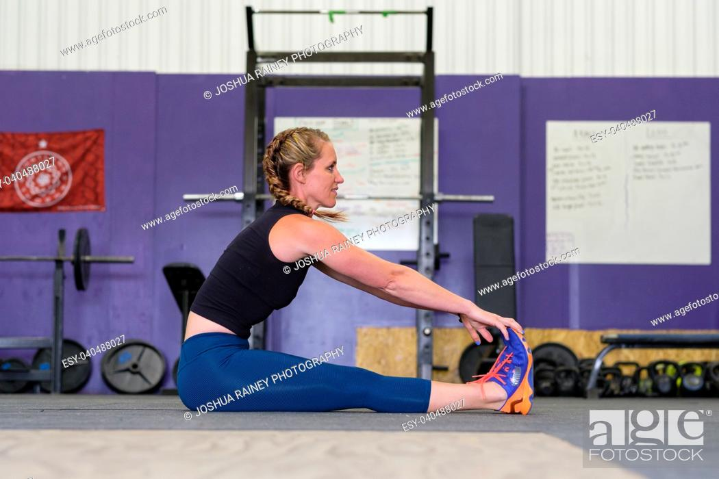 Stock Photo: Female stretching during a workout at a gym that focuses on crosstraining.