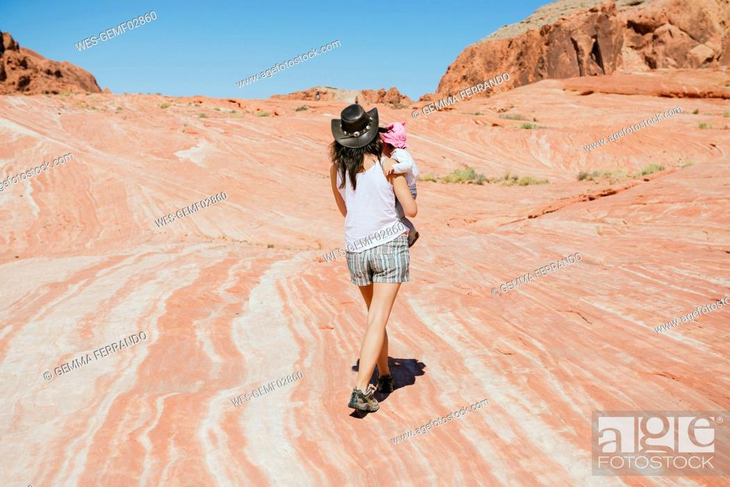 Stock Photo: USA, Nevada, Valley of Fire State Park, back view of mother with baby girl on her arms in reddish landscape.
