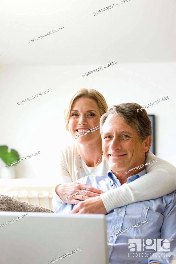 Stock Photo: Portrait of woman hugging man holding laptop.