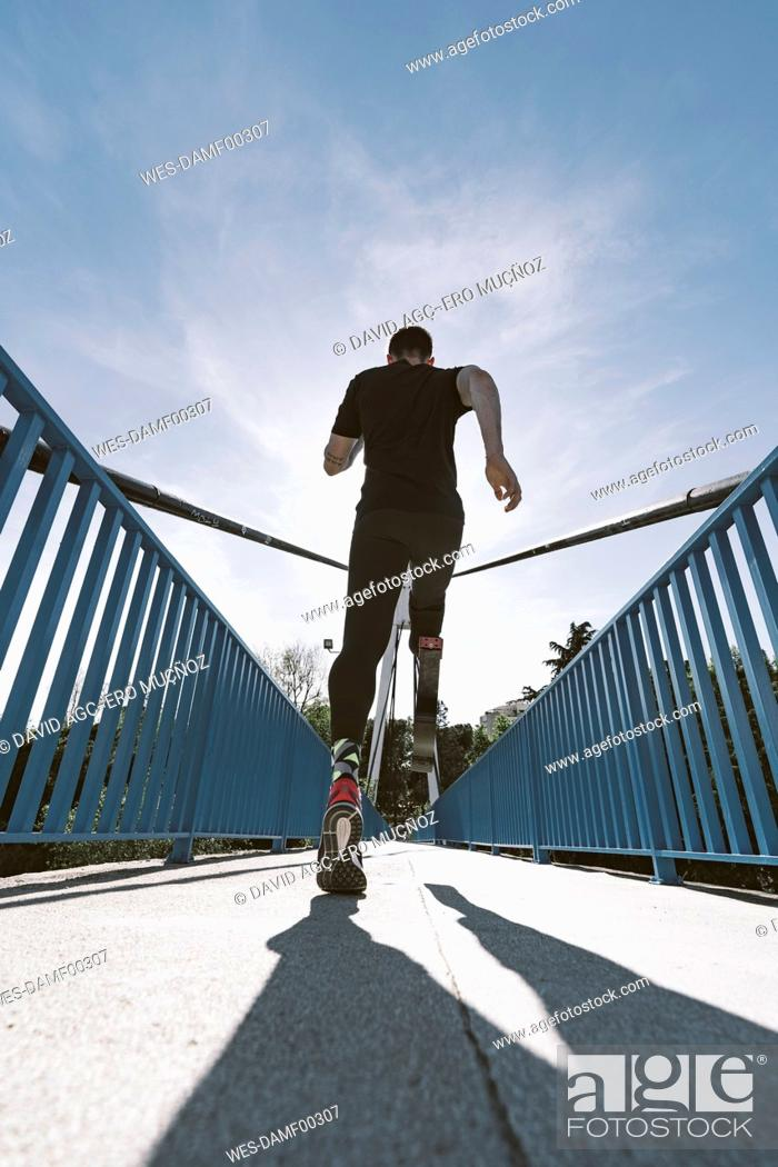 Photo de stock: Rear view of disabled athlete with leg prosthesis running on a bridge.