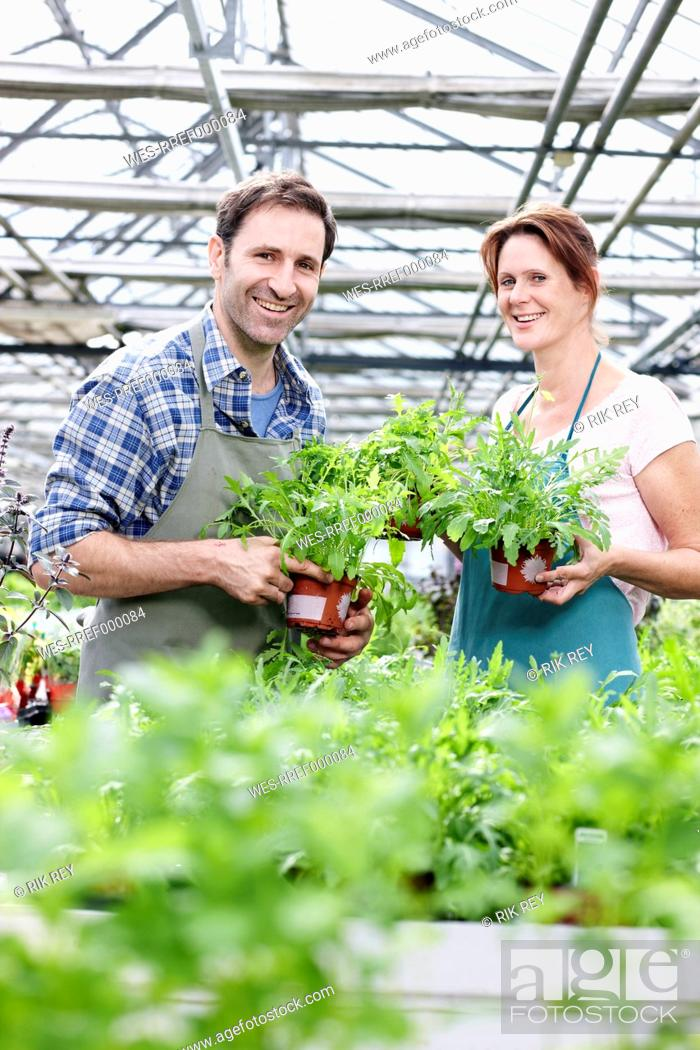 Stock Photo: Germany, Bavaria, Munich, Mature man and woman in greenhouse with rocket plant, smiling, portrait.