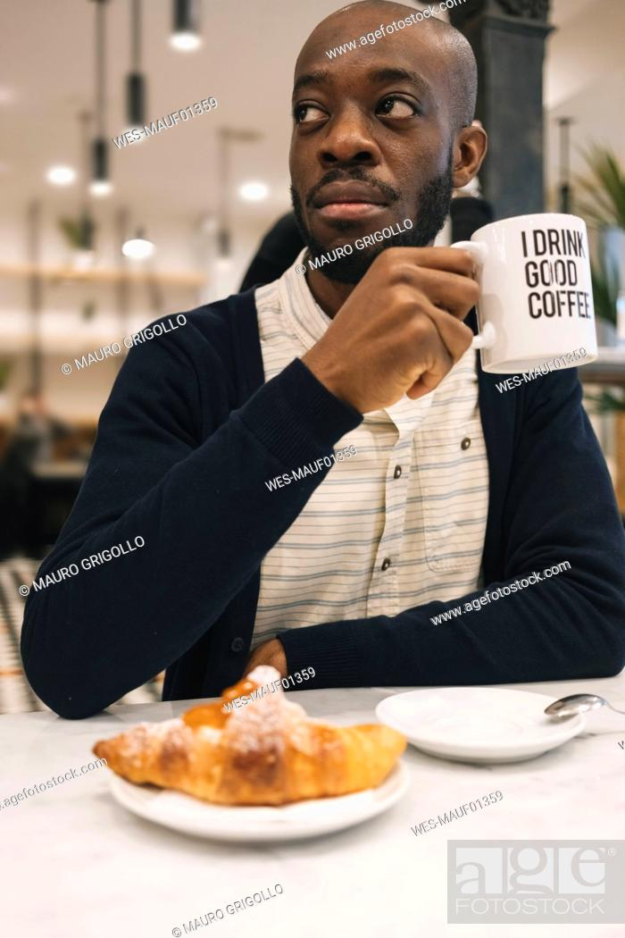 Stock Photo: Man with croissant and cup of coffee in a cafe looking around.
