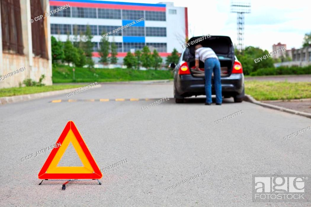 Stock Photo: Triangle warning sign on road foreground and driver in car luggage rack.