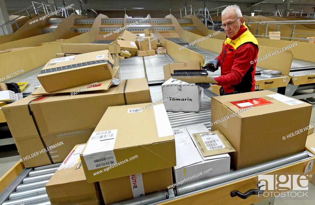 Stock Photo: Package deliverer Hans-Joachim Harnagel reads the code on a package with a scanner at the DHL delivery base Braunschweig, Germany, 21 December 2016.