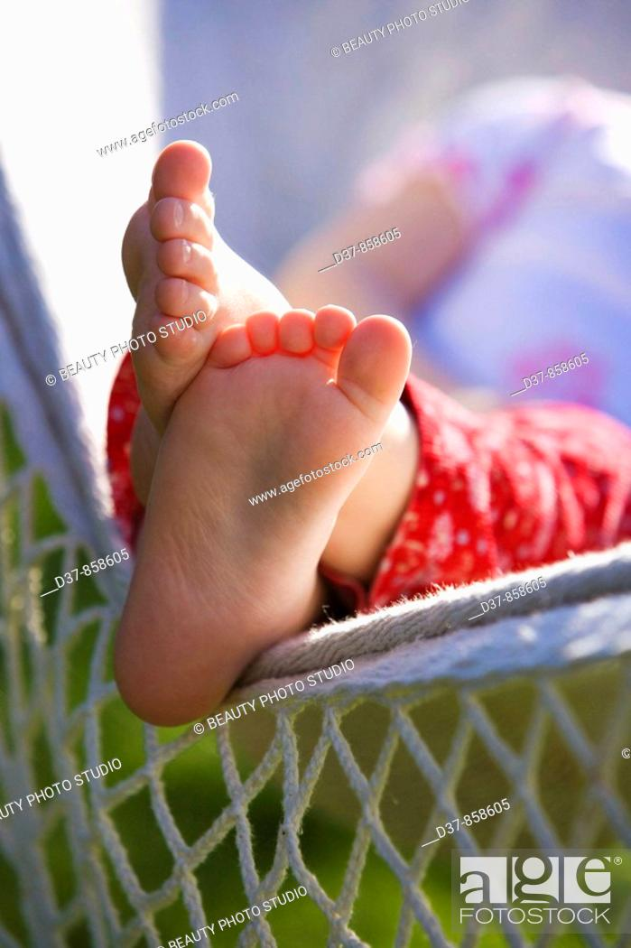 Stock Photo: Close up of a girl's feet resting on a hammock.