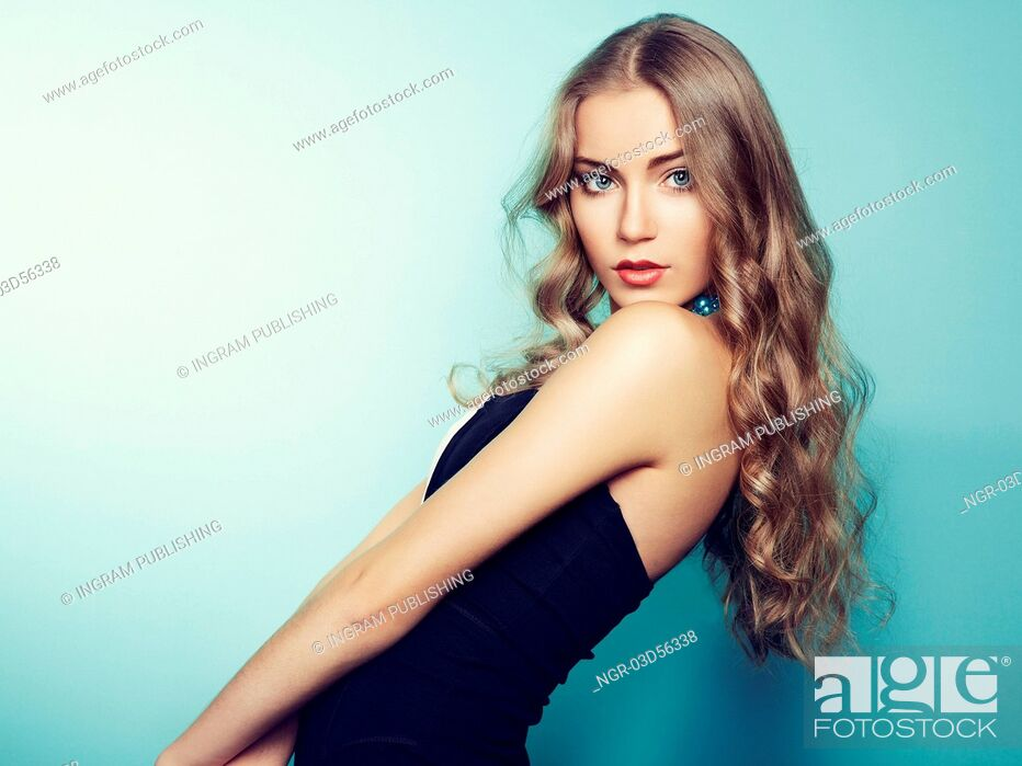 Stock Photo: Portrait of beautiful young blonde girl in black dress. Fashion photo.