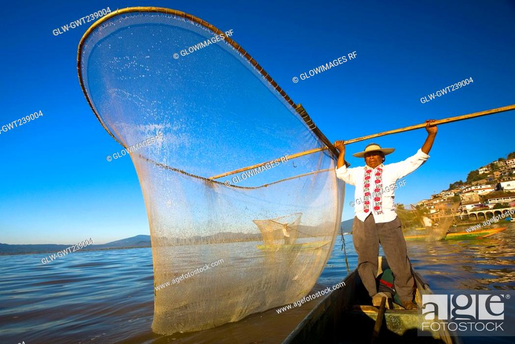Stock Photo: Fisherman with butterfly fishing net in a lake, Janitzio Island, Lake Patzcuaro, Patzcuaro, Michoacan State, Mexico.