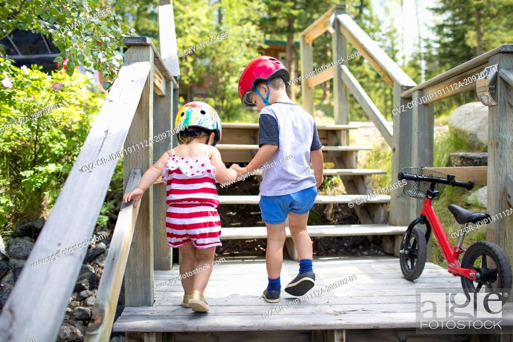 Stock Photo: Brother holding hands with sister helping her up wooden staircase.