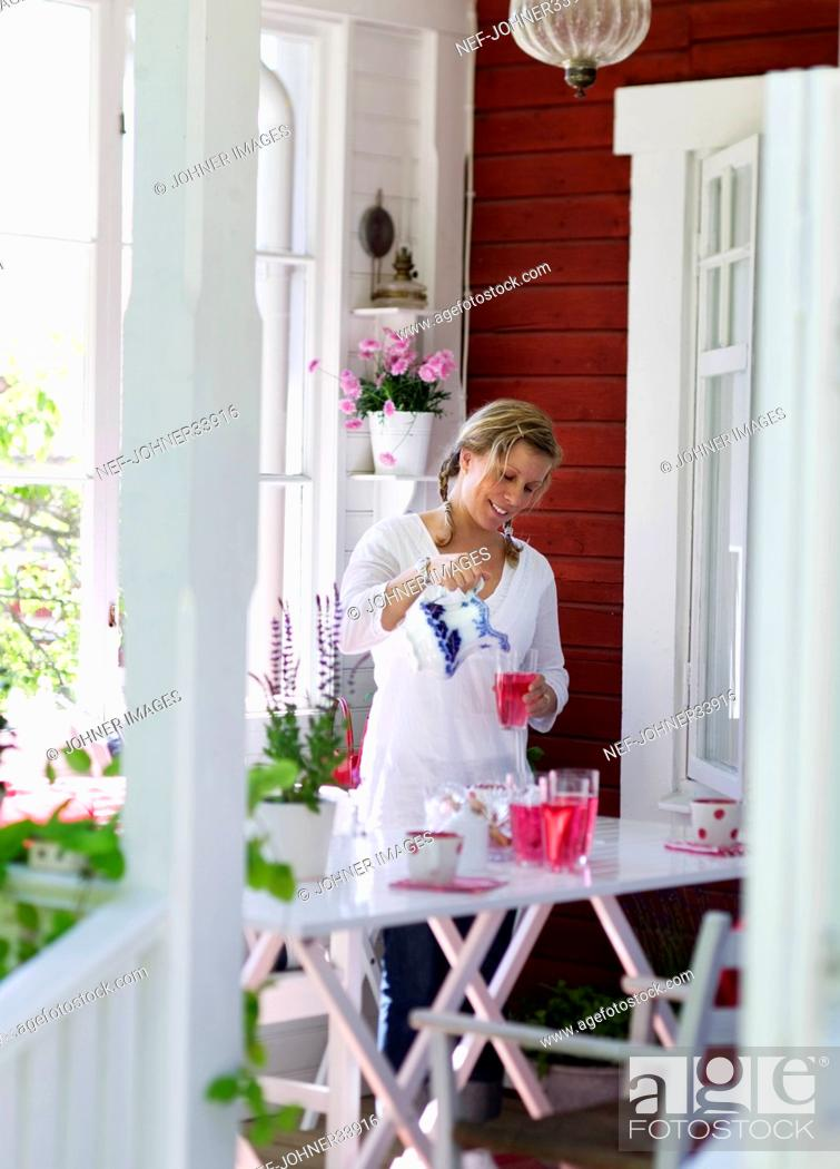 Imagen: Woman having drink on patio.