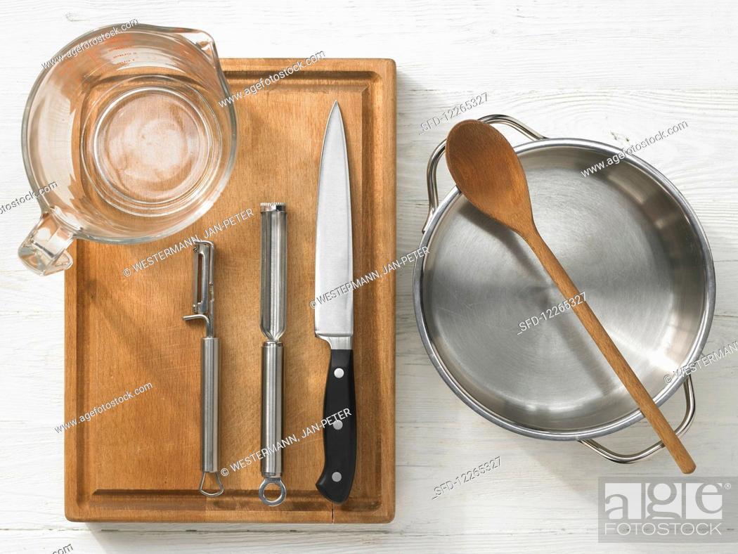 Stock Photo: Kitchen utensils: measuring cups, vegetable peeler, knives, pot, wooden spoon.