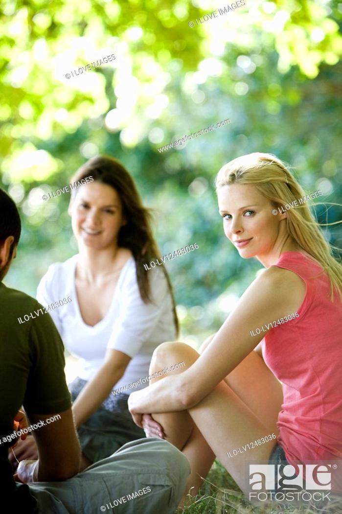 Stock Photo: Three friends sitting on the grass.