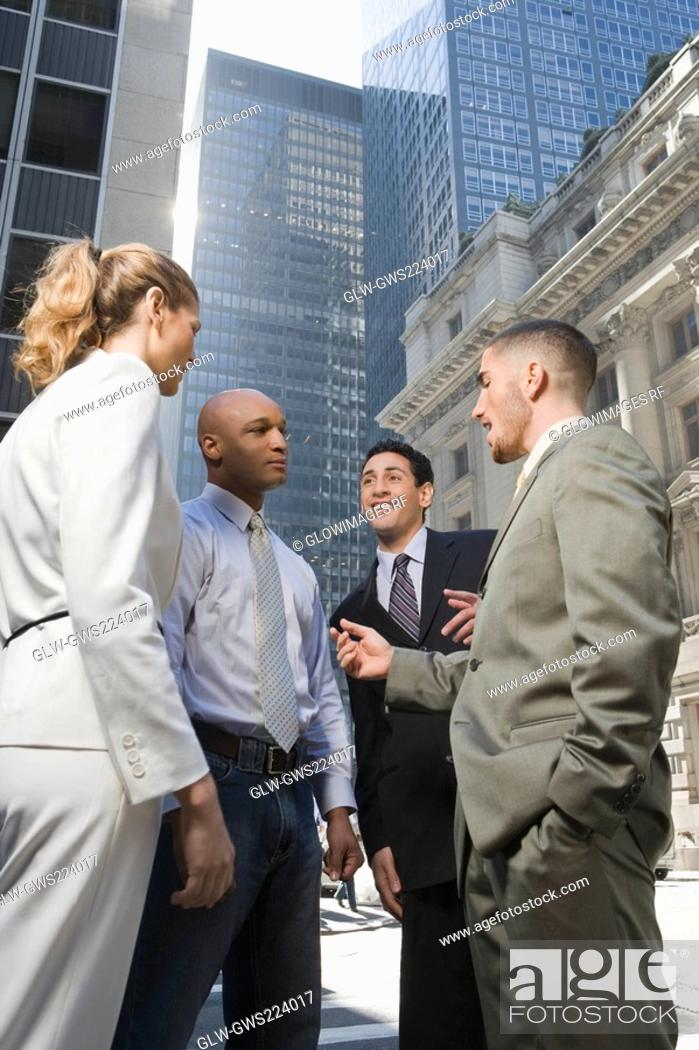 Stock Photo: Side profile of a businesswoman standing with three businessmen.