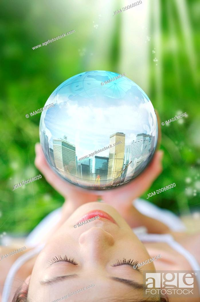 Stock Photo: Lohas, Environmental Conservation, Digitally generated image of woman hands holding a sphere with buildings in it.