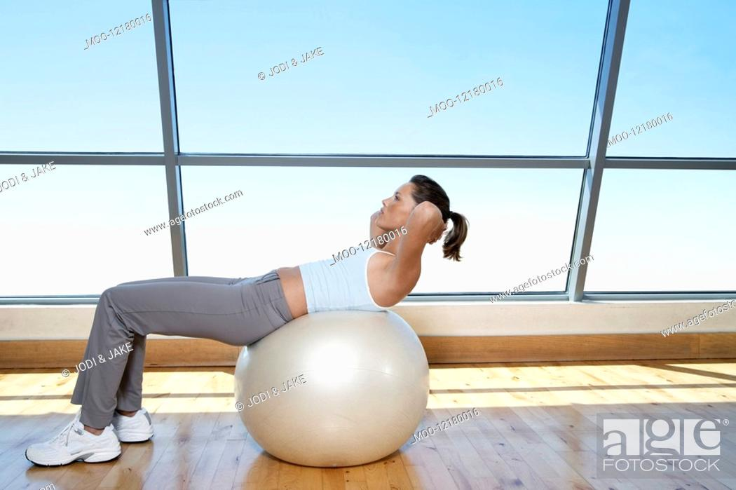 Stock Photo: Woman Doing Sit-Ups on exercise ball in gym.