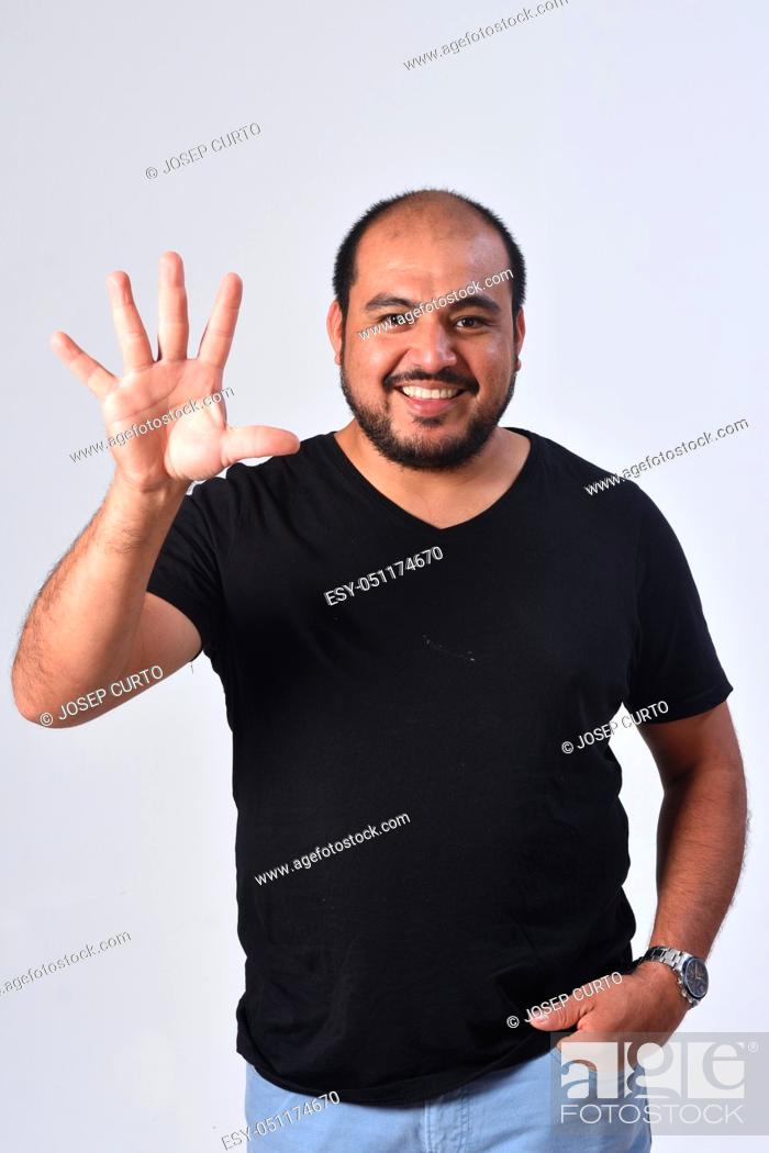 Stock Photo: latin american man with finger in the shape of number five.
