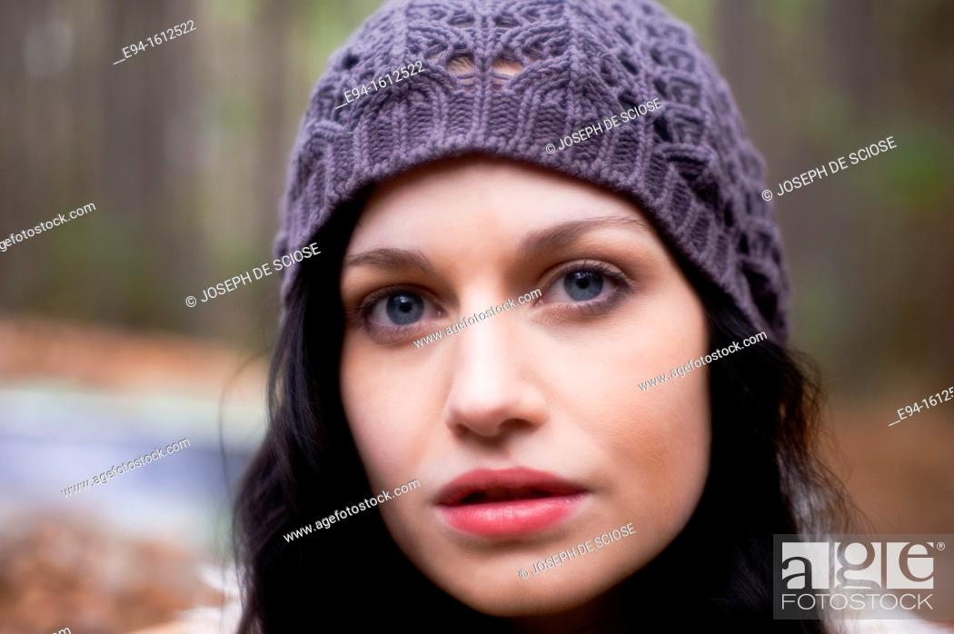 Stock Photo: Portrait of a 20 year old brunettte woman wearing a knit hat outdoors.