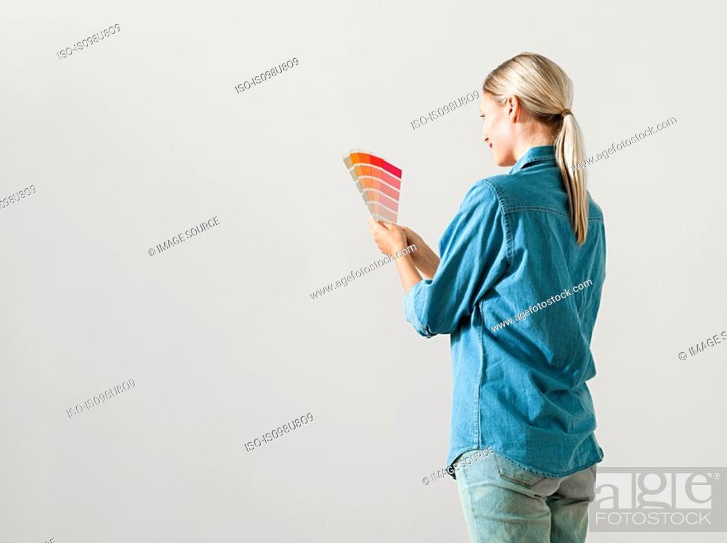 Stock Photo: Young woman choosing paint color.