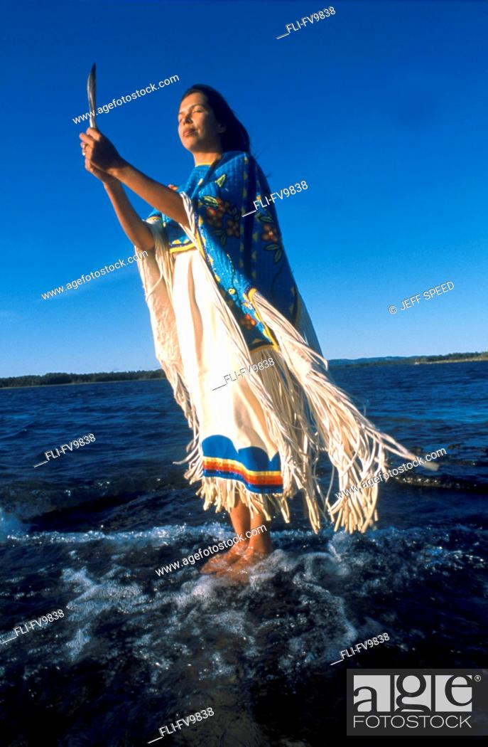 Stock Photo: Anishnawbe Woman standing on Rock in Water, Manitoulin Island, Ontario.