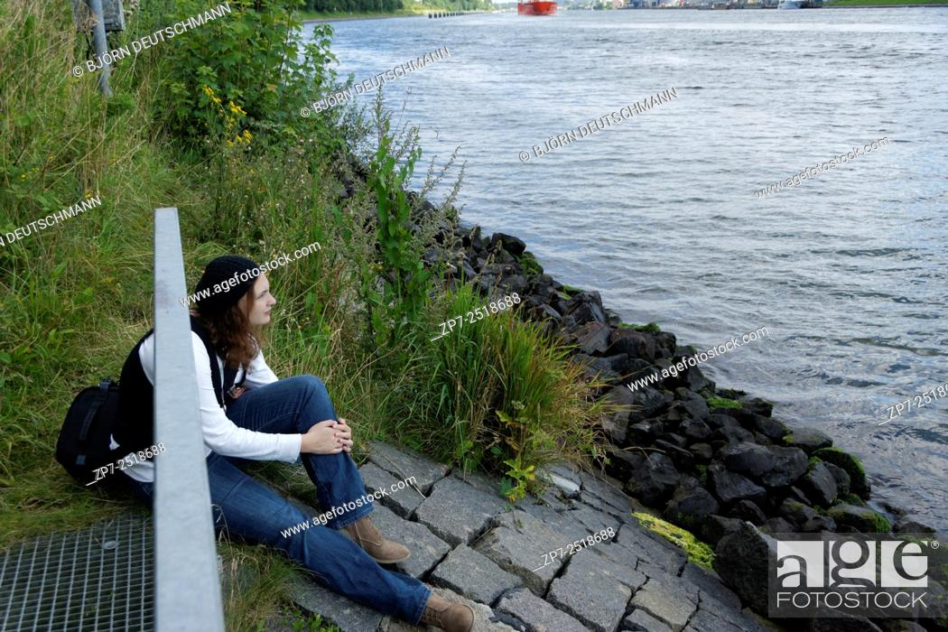Stock Photo: Teenager sitting at the water and is dreaming.