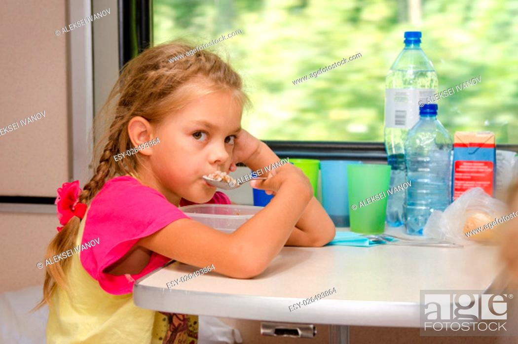 Stock Photo: A six-year girl in a train sitting at the table on the lower place in the second-class compartment of the car and eats porridge spoon.