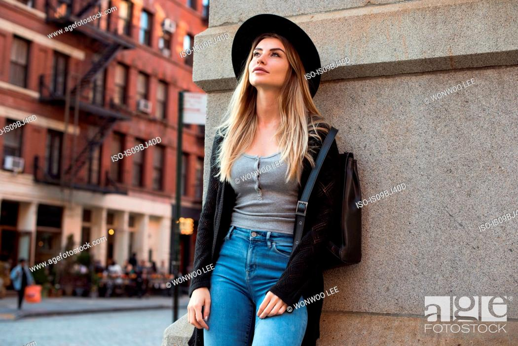 Stock Photo: Portrait of woman leaning against wall looking up, New York, USA.