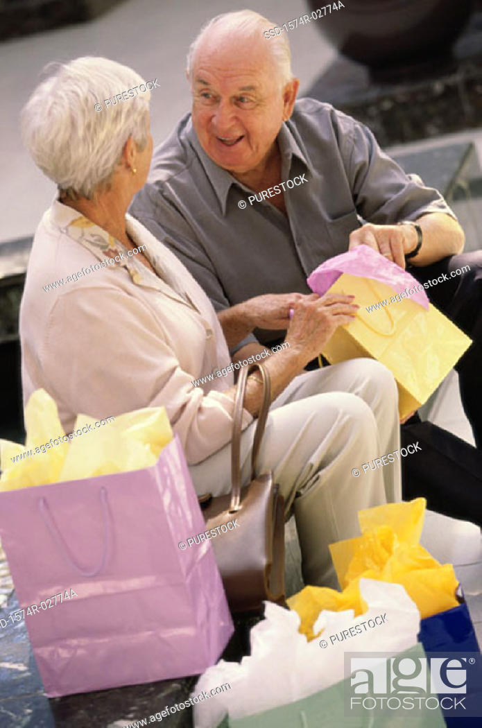 Stock Photo: Senior couple sitting together looking into shopping bags.