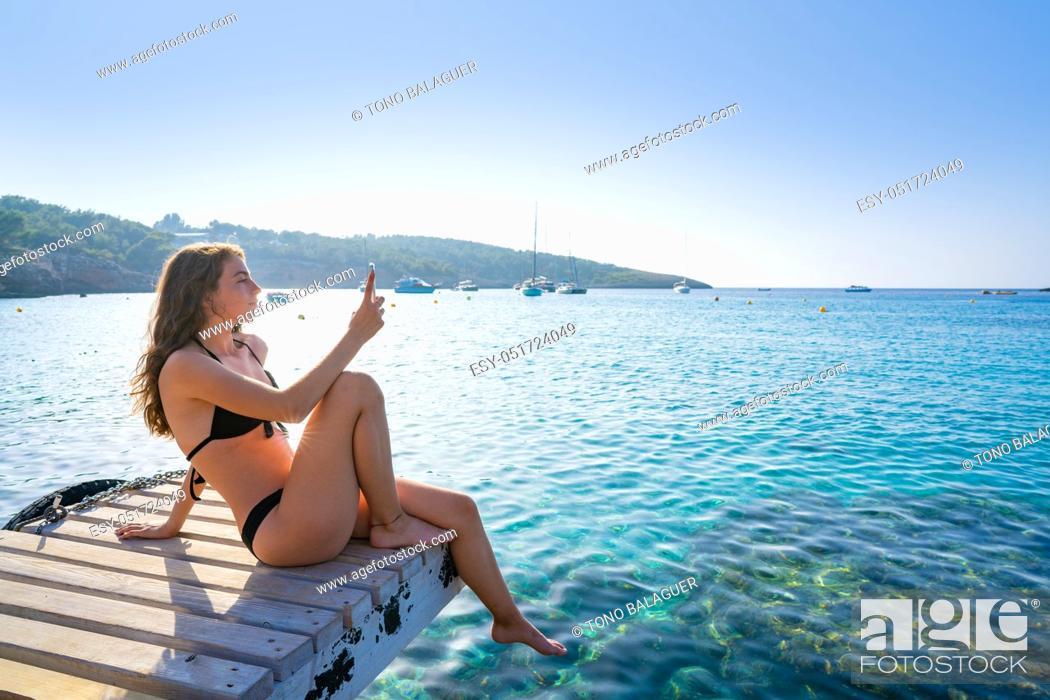 Stock Photo: Ibiza girl taking smartphone photos at Portinatx beach pier in Balearic Islands.