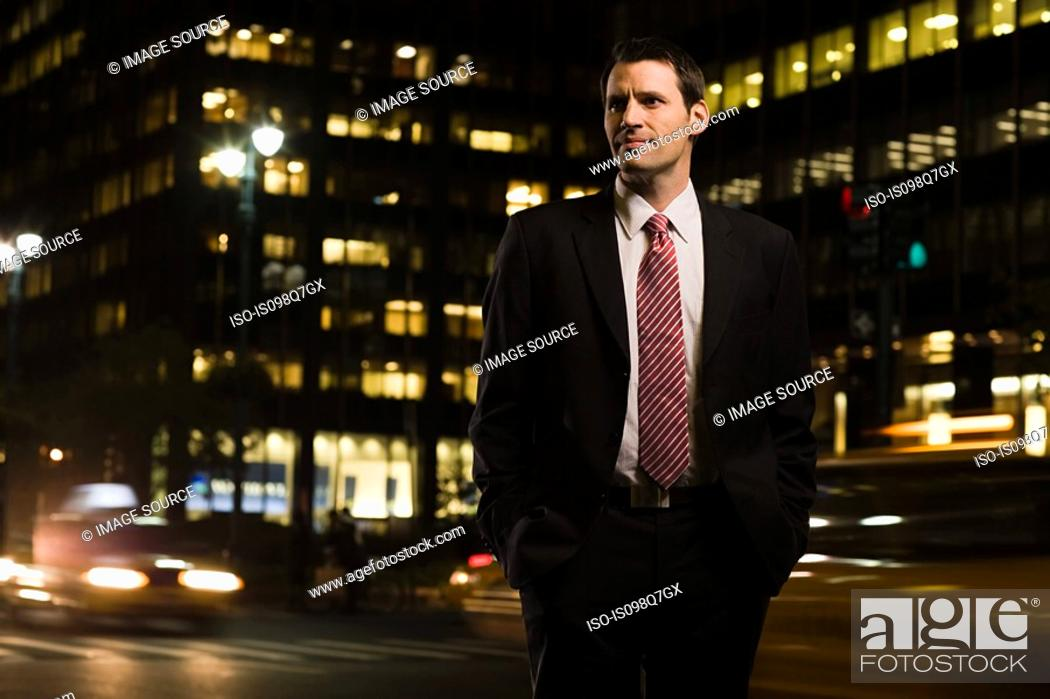 Stock Photo: Businessman standing near a busy road.