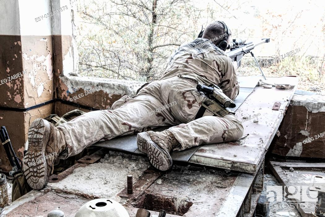 Imagen: Portrait of U. S. Navy SEAL sniper on firing position, armed with large caliber sniper rifle with telescopic sight, wearing tactical headset with microphone.