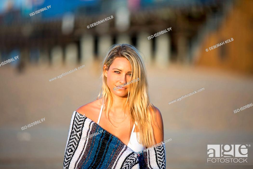 Stock Photo: Portrait of sultry young woman wrapped in blanket on beach, Santa Monica, California, USA.