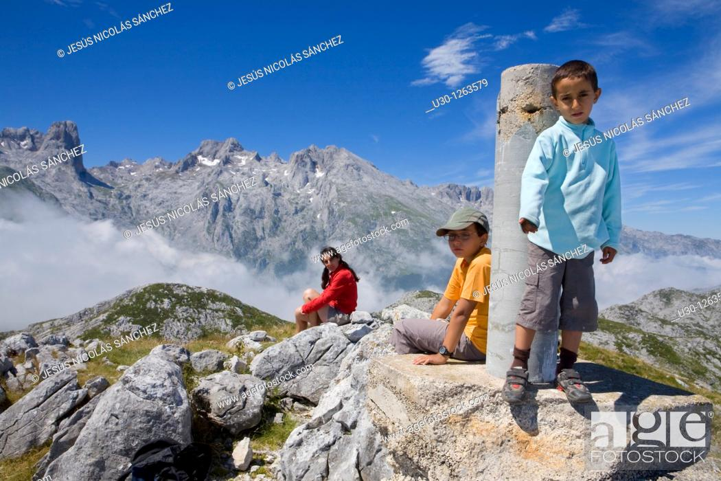 Stock Photo: Family in the summit of Peña Maín next to a gedesic vertex, Urrieles massif, in the Picos de Europa National Park, Asturias, Spain.
