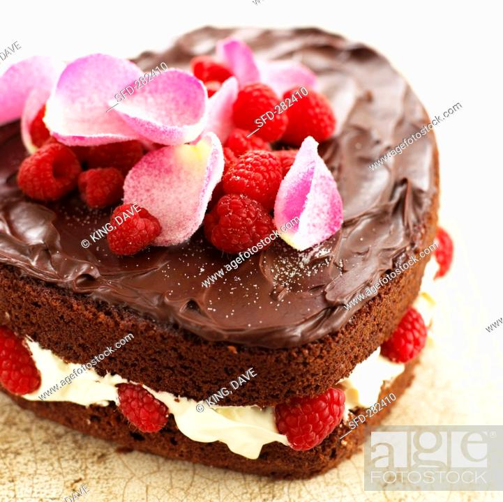 Stock Photo: Heart-shaped chocolate cake with raspberries, cream and rose petals.