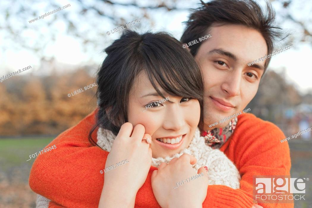 Imagen: Smiling young couple embracing in park during winter.