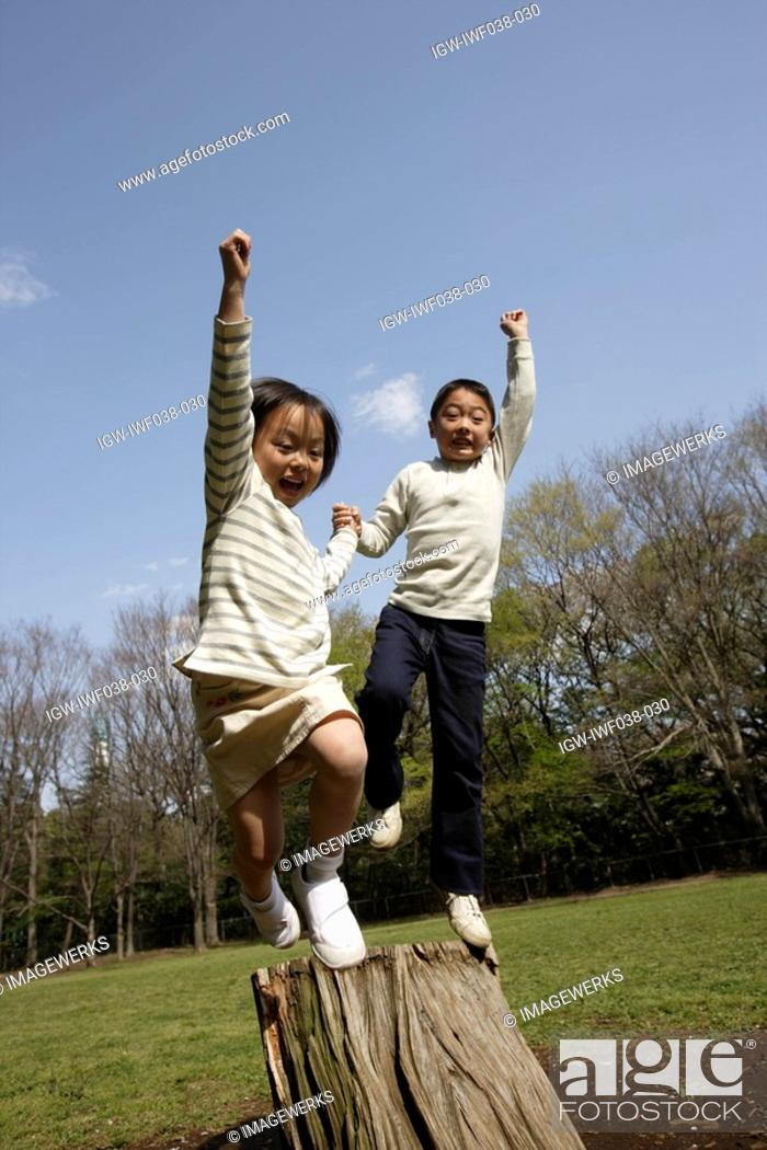 Stock Photo: Children jumping from wooden log.